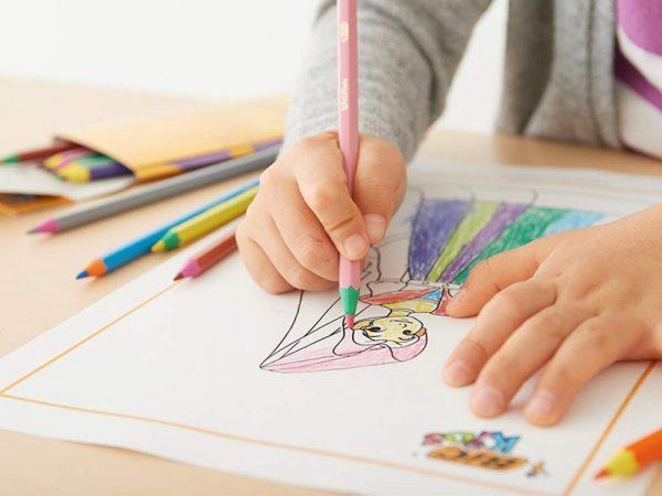 Uma criança está pintando com lápis de cor um desenho numa folha sulfite