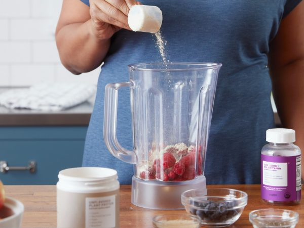 AltText: Imagem de uma mulher colocando suplementos e frutas no liquidificador