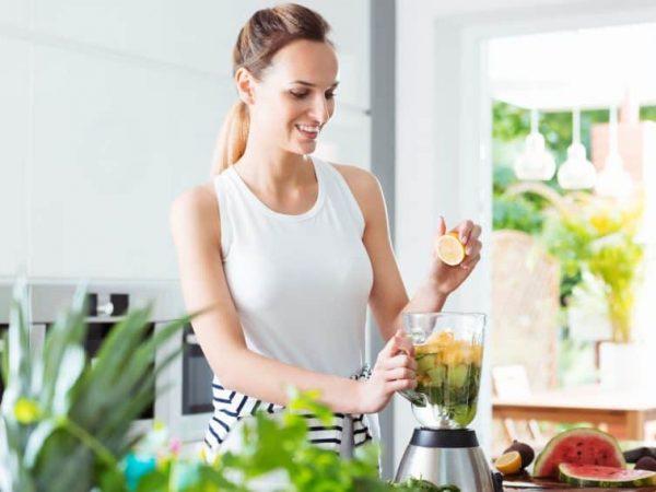 Na foto uma mulher preparando um suco no liquidificador.