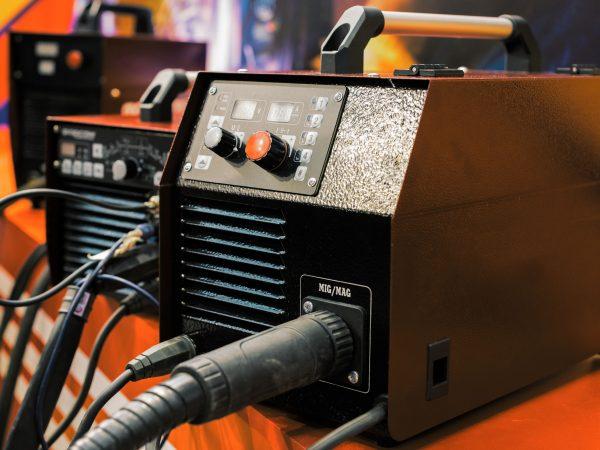 Imagem mostra uma máquina de solda MIG sobre uma prateleira.