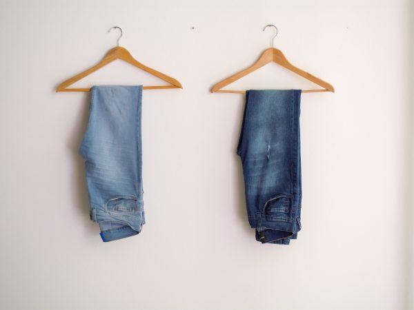 Foto de dois cabides de madeira pendurados em uma parede branca com uma calça jeans em cada. Uma das calças é clara e a outra escura.