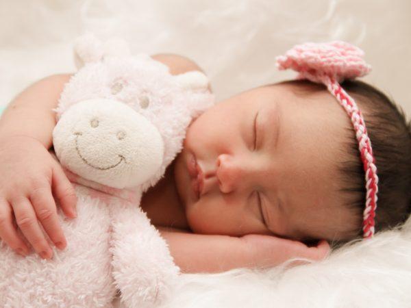 Imagem de um bebê dormindo com a naninha.