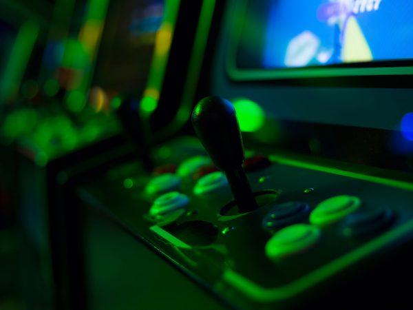 Plano detalhe dos controles de um arcade, com uma fileira de arcades ao fundo, desfocados.