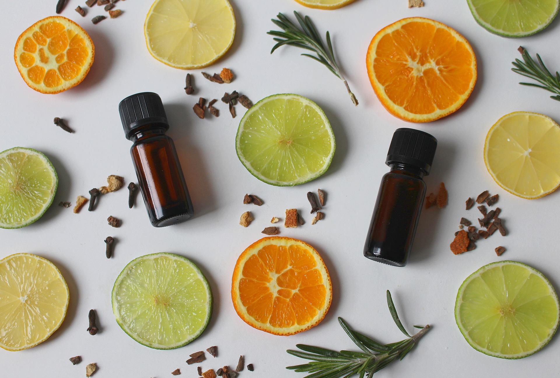 Imagem de várias rodelas de limão, cravos, especiarias e um frasco de vidro