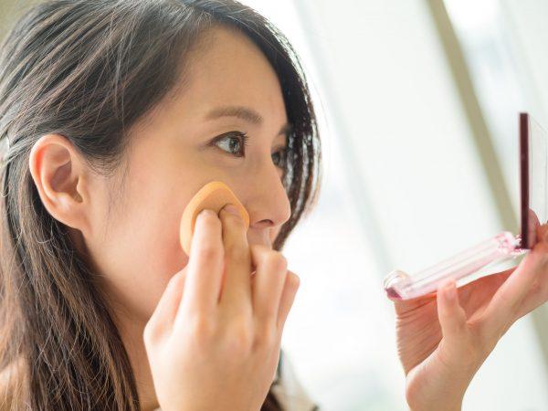 (Moça se maquiando com pancake enquanto olha no espelho)