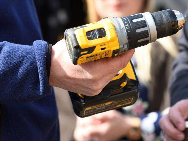 Imagem mostra uma parafusadeira DeWalt nas mãos de uma pessoa.