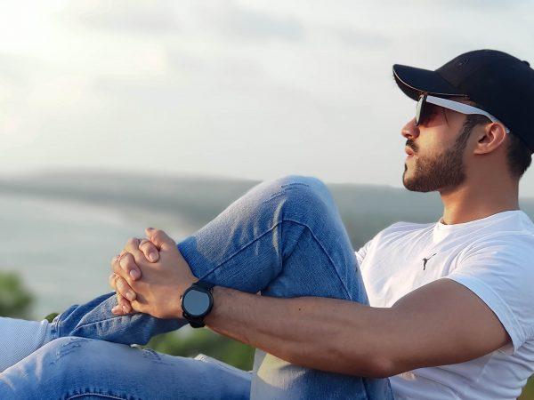 Na foto um homem olhando para o horizonte em um lugar alto vestindo uma calça jeans masculina.