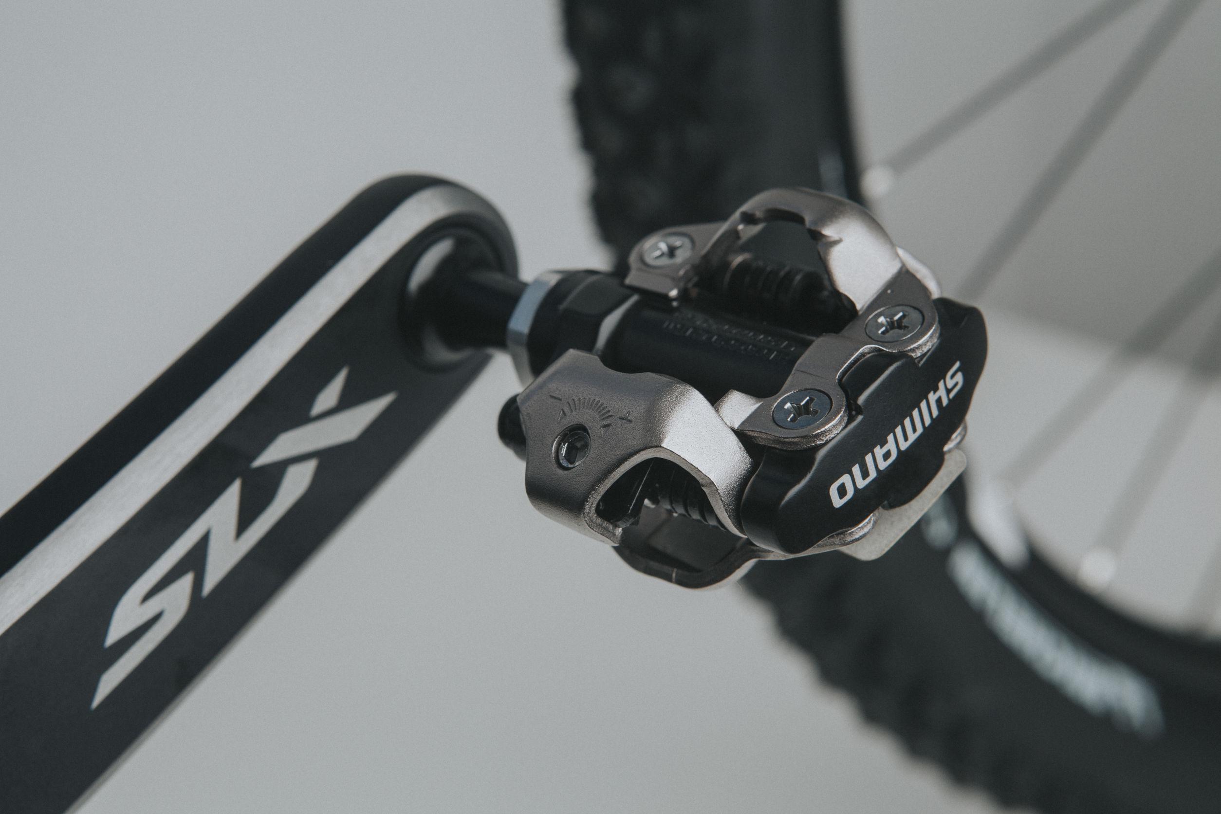 Imagem mostra um pedal Shimano em foco seletivo, com um pneu ao fundo, desfocado.