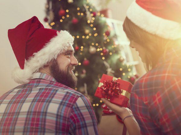 Na foto uma mulher entregando um presente para um homem.