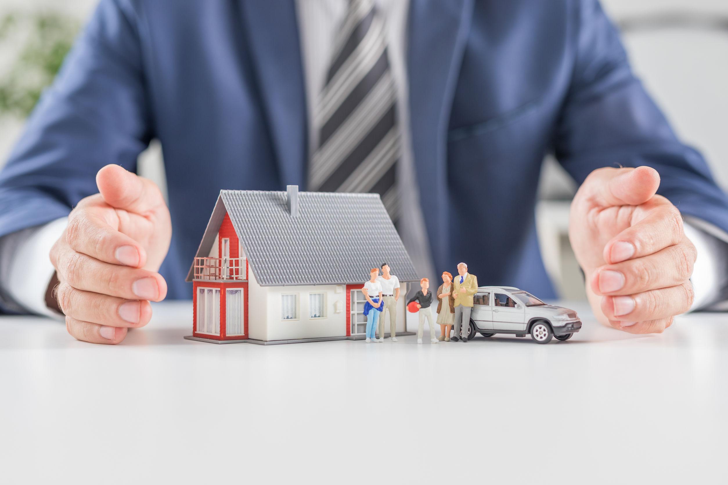 Homem de terno e gravata mostrando maquete de casa, família e carro.
