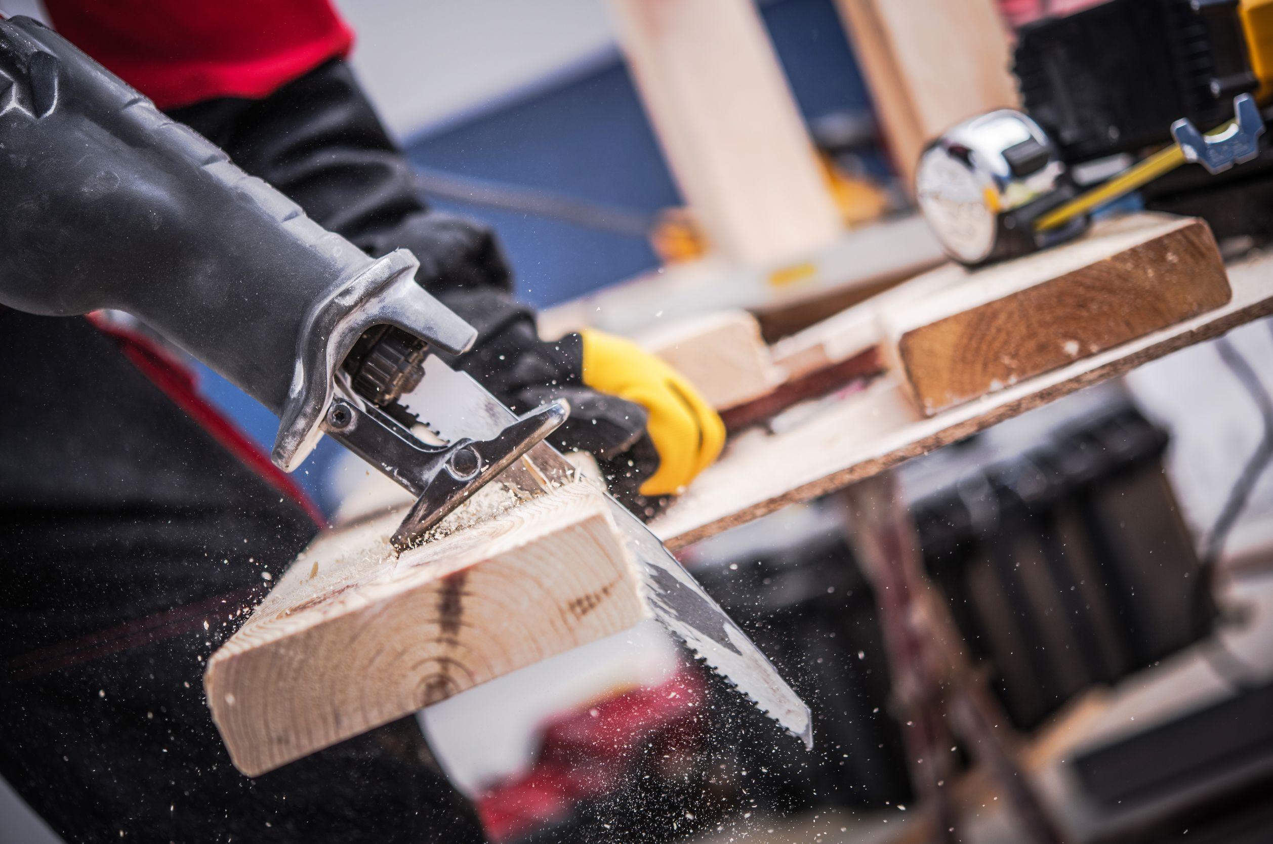 Imagem mostra uma serra sabre sendo usada para cortar um pedaço de madeira.