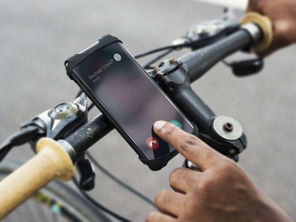 Pessoa faz ligação de celular no suporte de celular para bicicleta enquanto pedala