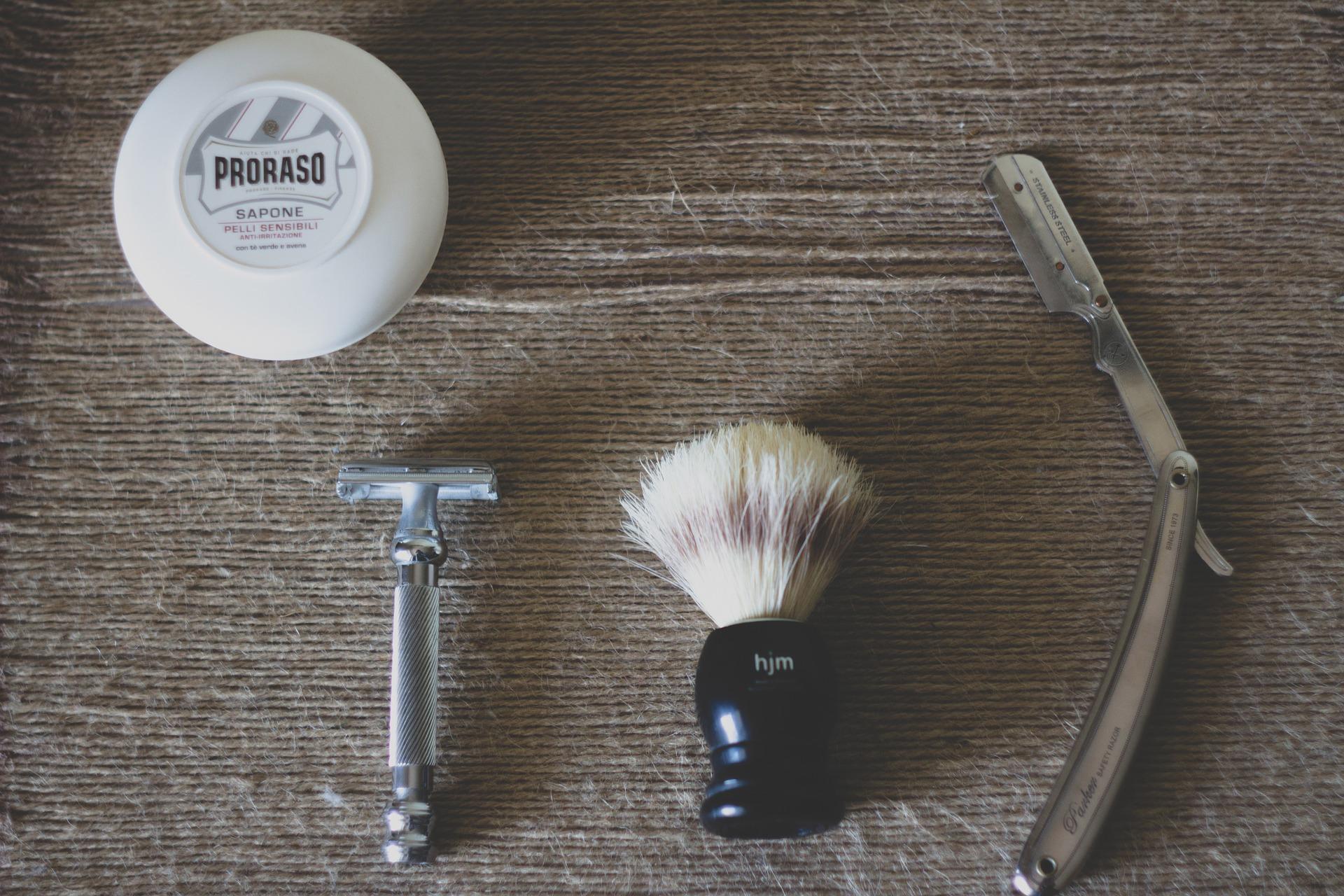 Navalha ao lado de pincel e demais acessórios para barbear