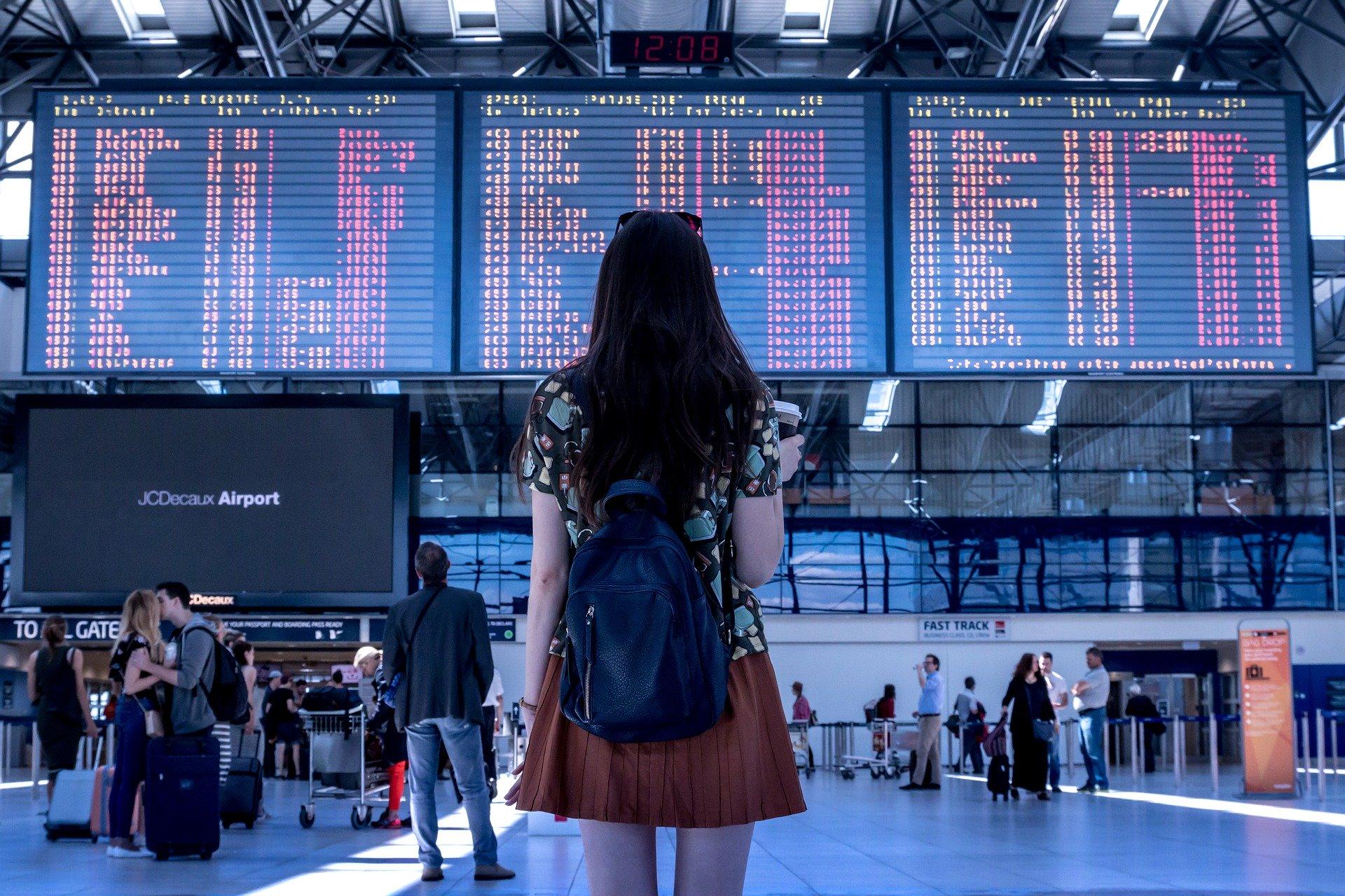 Mulher de costas olhando para painel de voos no aeroporto.