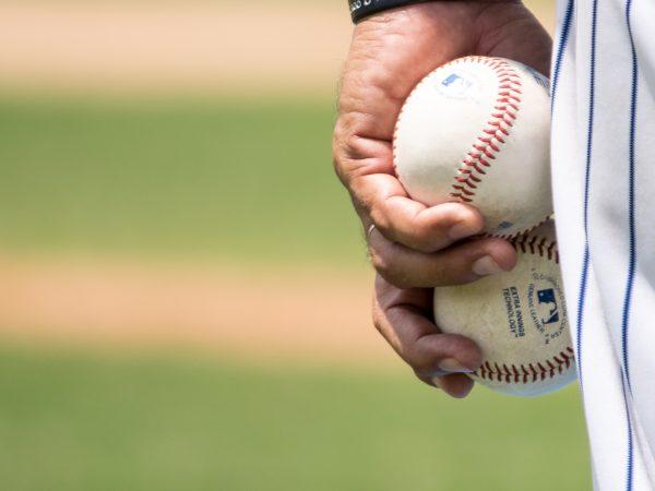 Imagem mostra a mão esquerda de um jogador segurando duas bolas de beisebol rente à sua perna , apoiando-as entre a palma e a coxa.