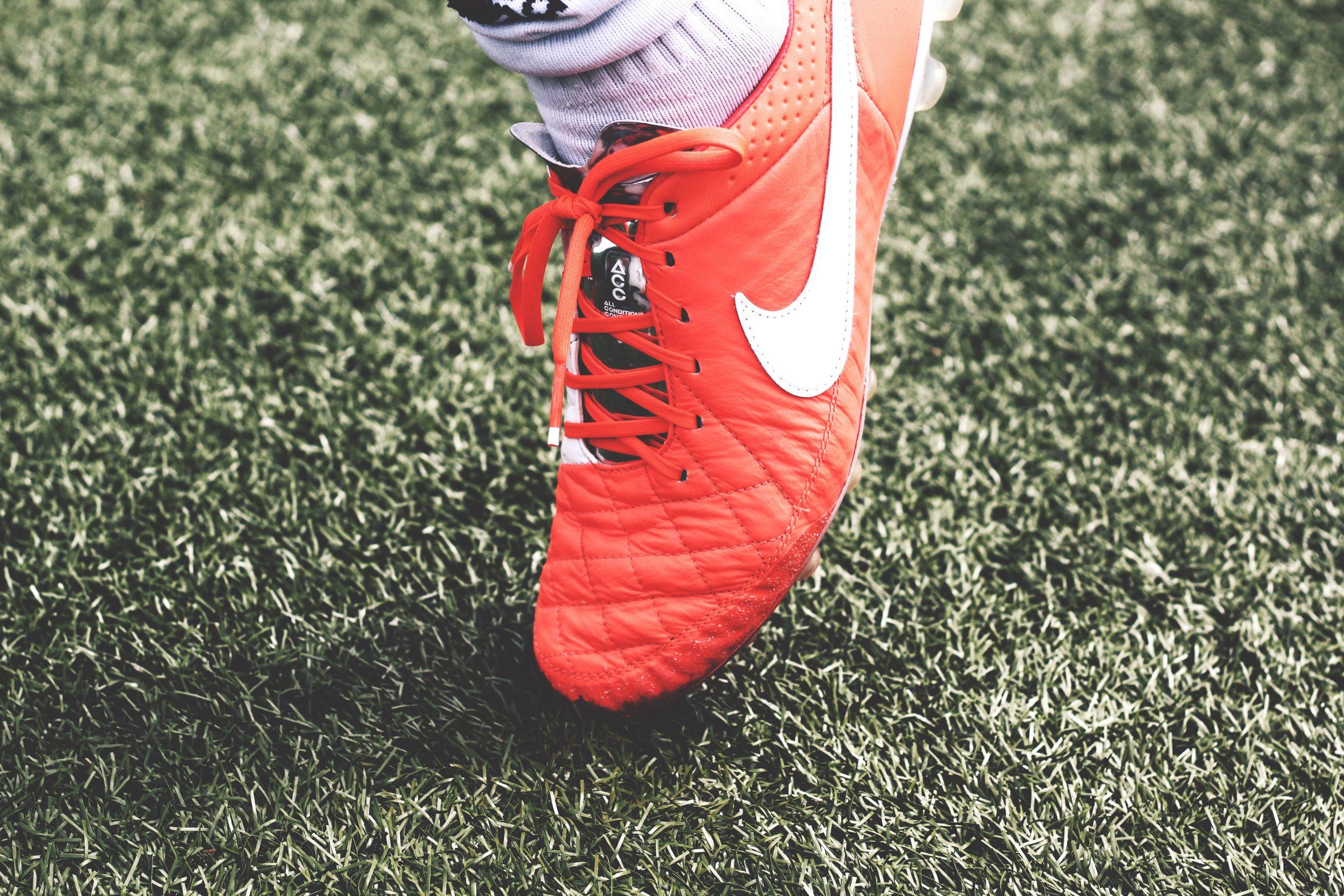 Imagem mostra um pé calçado de uma chuteira Nike, que apoia seu bico num gramado baixo.