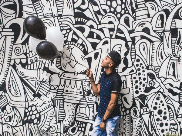 Imagem mostra um homem, usando um boné preto e branco, segurando bexigas preto e brancas, e posando na frente de um muro grafitado, também preto e branco