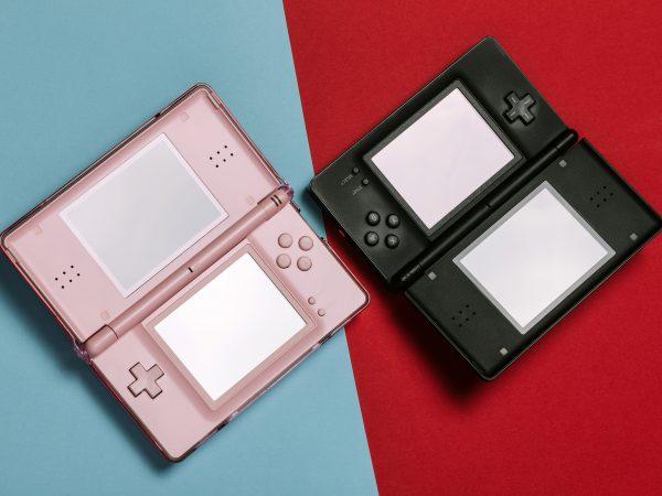 Imagem mostra dois Nintendo 3DS abertos e desligados lado a lado, um preto e outro branco, sob uma superfície bicolor.