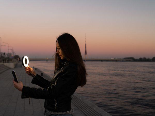 Mulher fotografando com ring light.