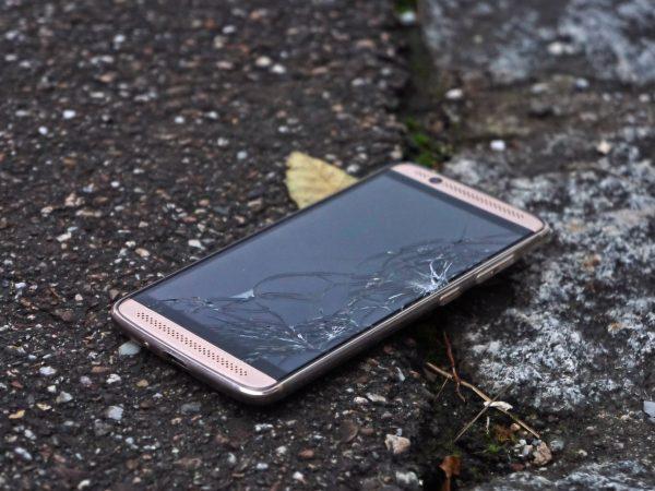 Imagem de um celular com a tela quebrada caído no chão