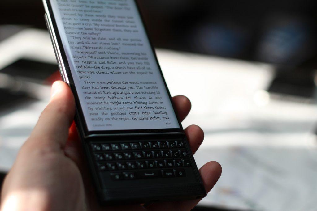Foto de um Blackberry apresentando um texto na tela, segurado por uma mão humana.