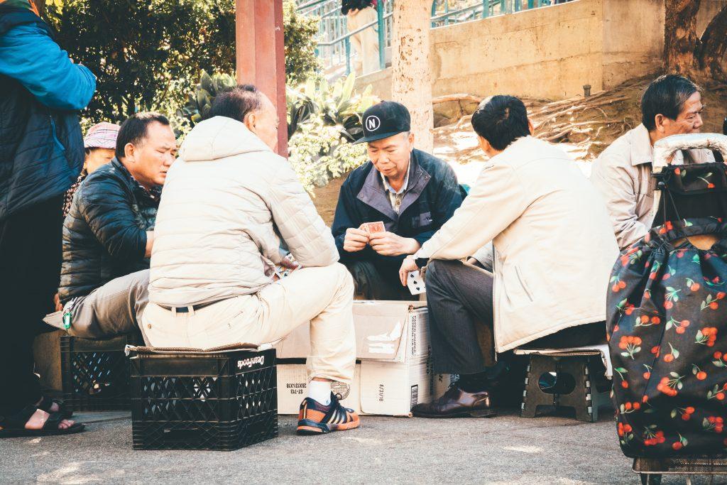 Imagem mostra um jogo de baralho improvisado, com quatro idosos, sentados em caixas de feira, usando uma caixa de papelão como mesa.