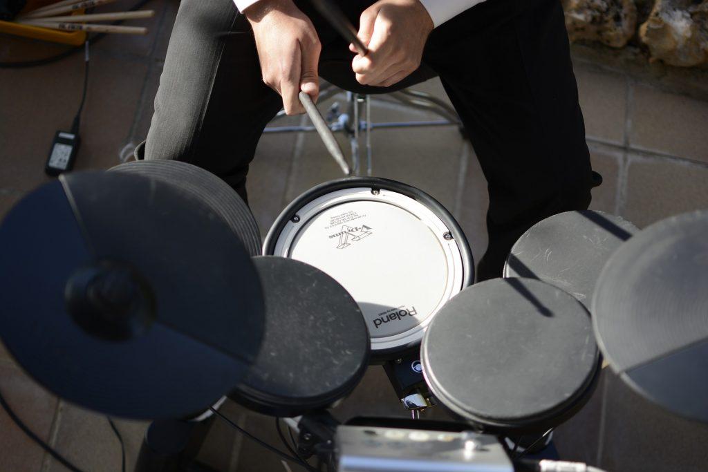 Detalhe de homem tocando bateria eletrônica.