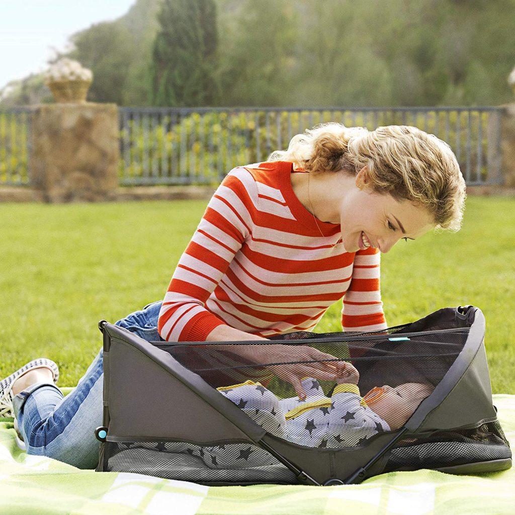 Mãe no chão do parque conversando com seu bebê que está deitado em um berço portátil