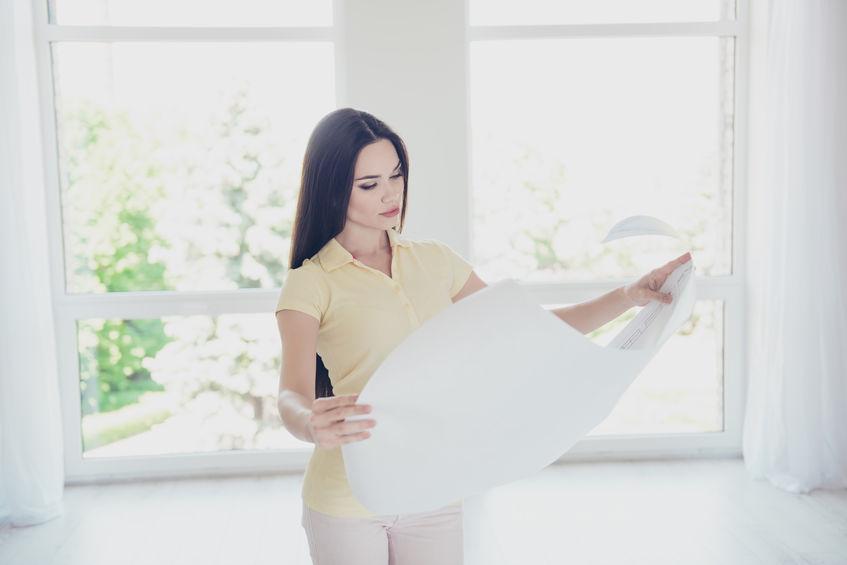 Imagem mostra uma mulher segurando um grande cartaz vendo um projeto