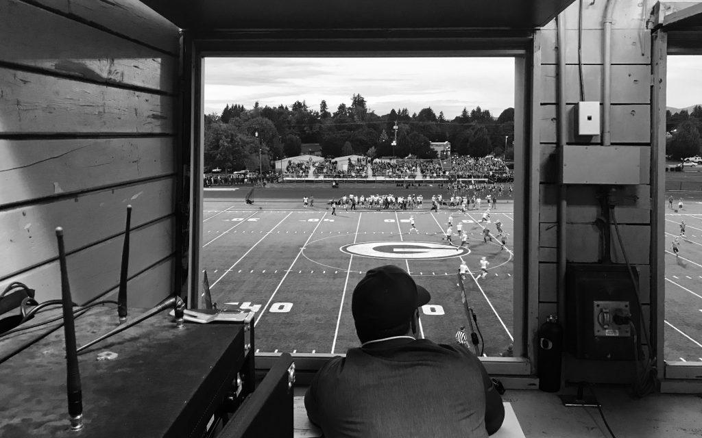 Imagem mostra um homem de boné assistindo um jogo de futebol americano pela janela de uma cabine de transmissão.