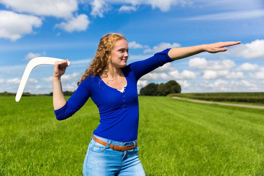 Imagem de mulher em campo aberto pronta para lançar um bumerangue de madeira