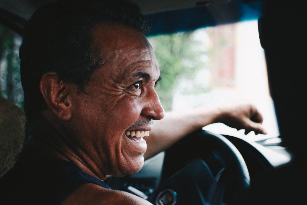 Um homem sorrindo com o braço esquerdo pendurado no volante do carro