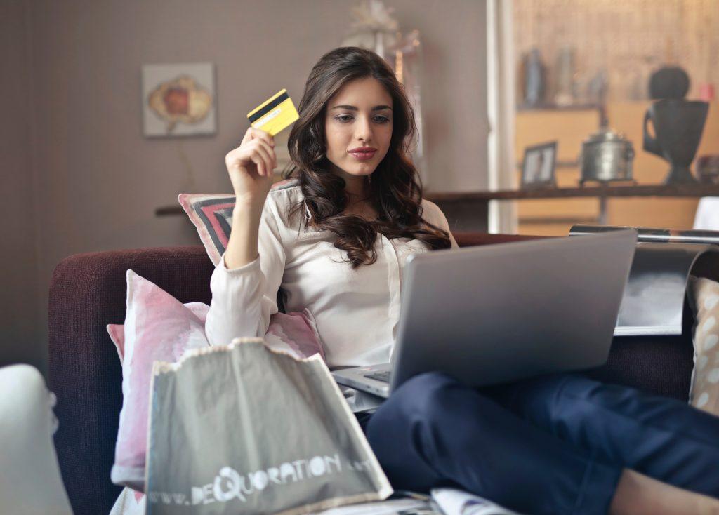 Mulher segurando o cartão, com o notebook no colo.