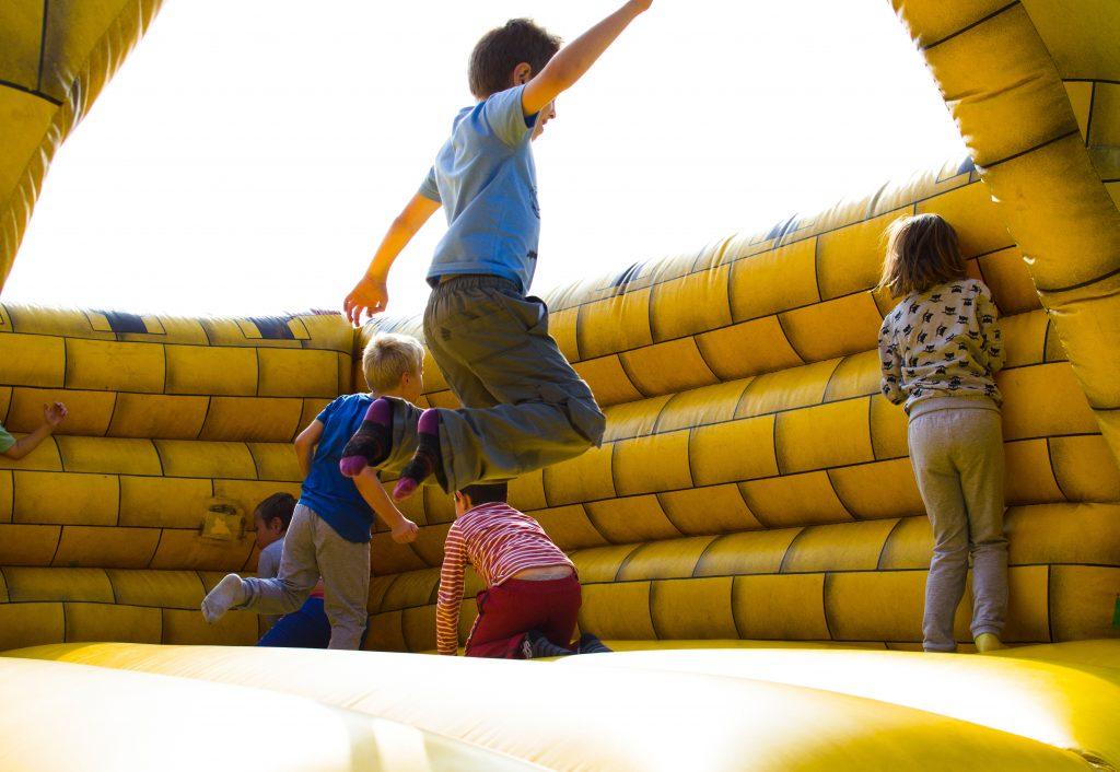 Grupo de crianças se diverte pulando em castelo inflável gigante