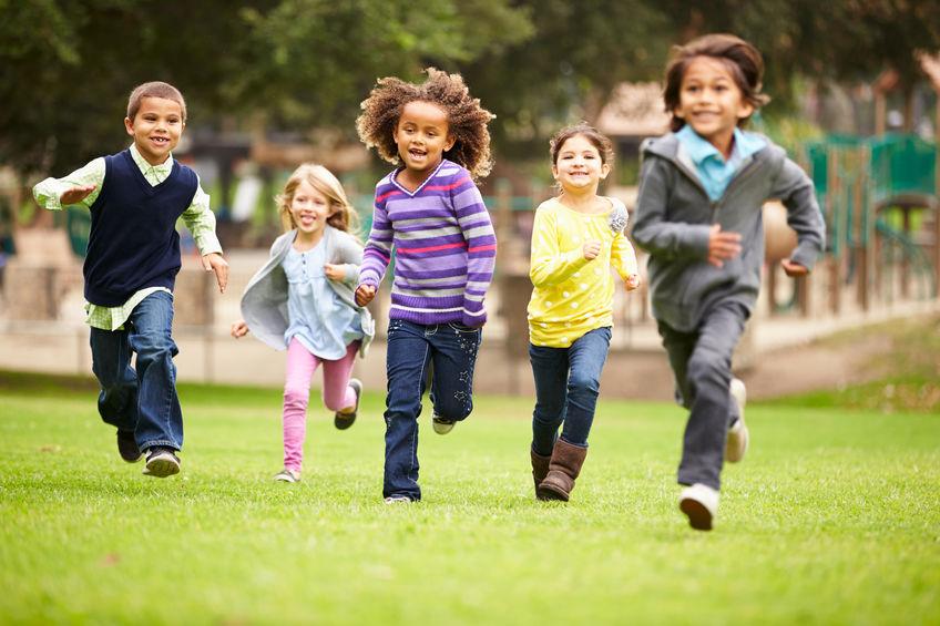 Crianças correndo na grama.
