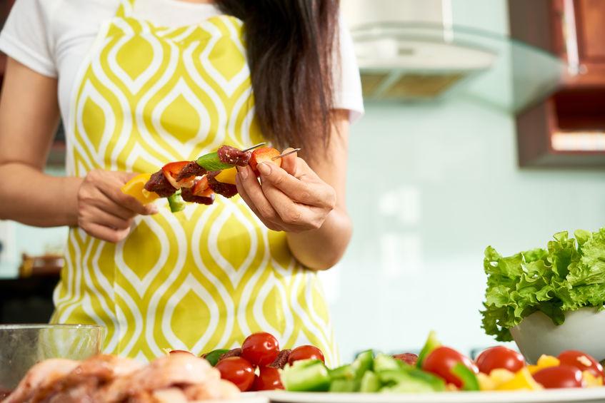 Na foto é possível ver uma mulher com roupa listrada preparando espetinhos de legumes.