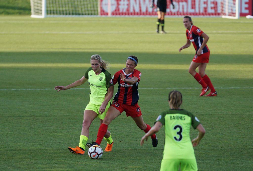 Imagem mostra o momento de um jogo em que duas adversárias disputam a bola na intermediária, observadas por duas outras jogadoras, uma que está de costas para a câmera, em primeiro plano, e outra que está em segundo plano e de frente para a câmera.