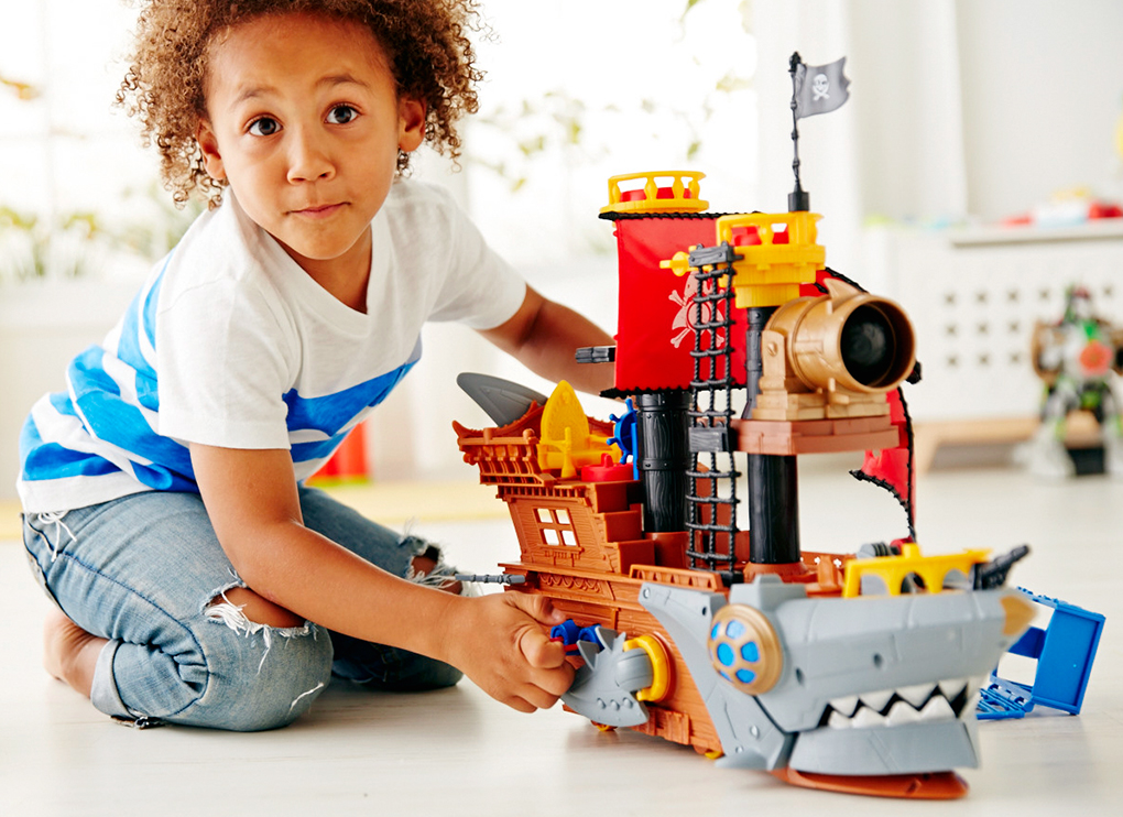 Na foto um menino brincando com um navio pirata.
