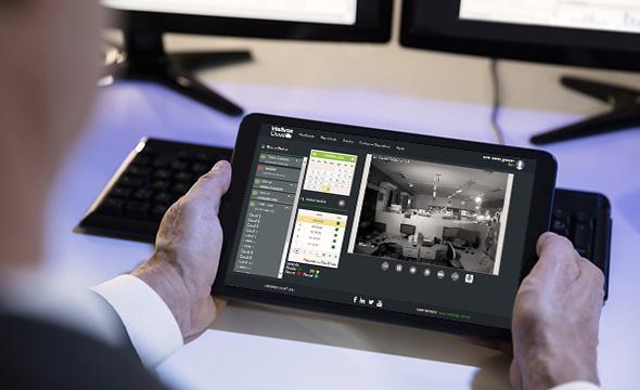 Imagem de uma pessoa acompanhando as imagens de uma câmera de segurança pelo tablet.