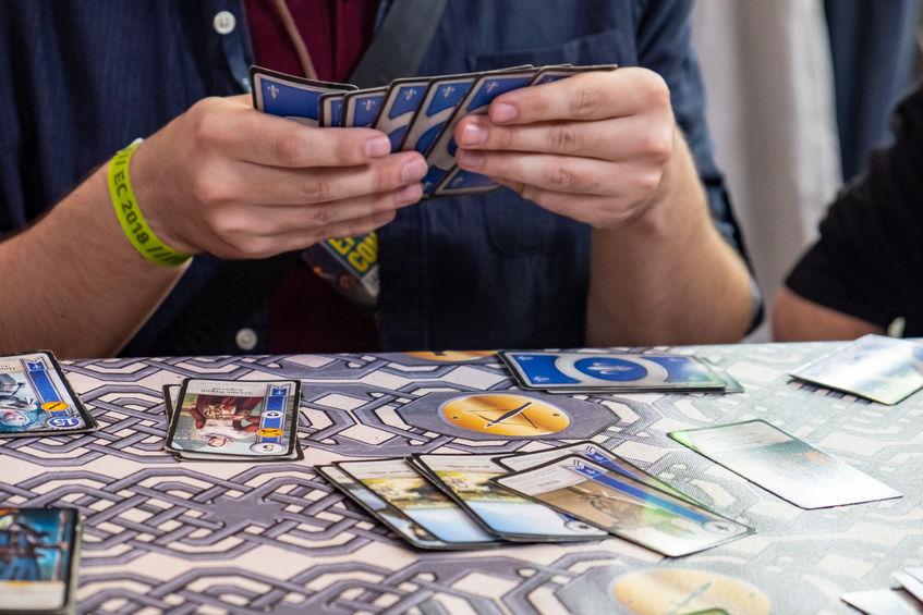 Um homem está segurando um baralho de cartas enquanto joga.