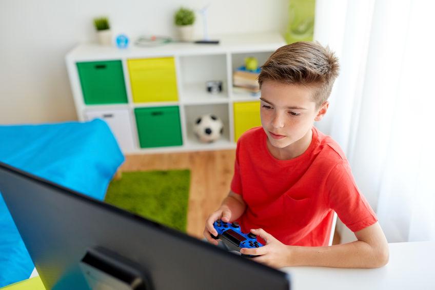 Na foto um menino dentro de um quarto jogando videogame.
