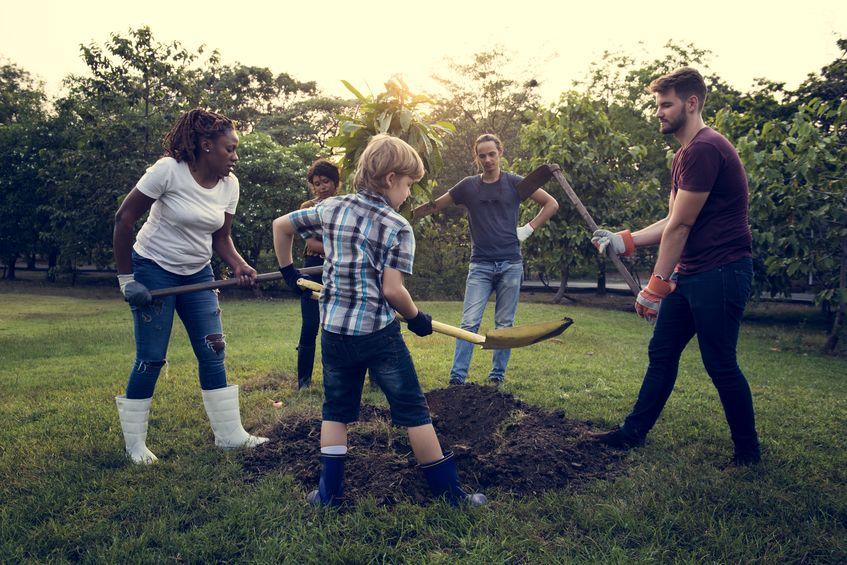 Há 5 pessoas formando um círculo ao redor de um pequeno monte de terra. Algumas pessoas estão usando enxadas e outras utilizam pá