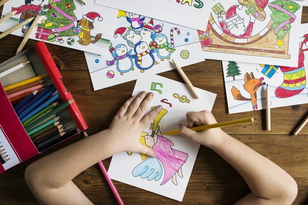 Mãos de criança colorindo desenhos em folhas sulfite