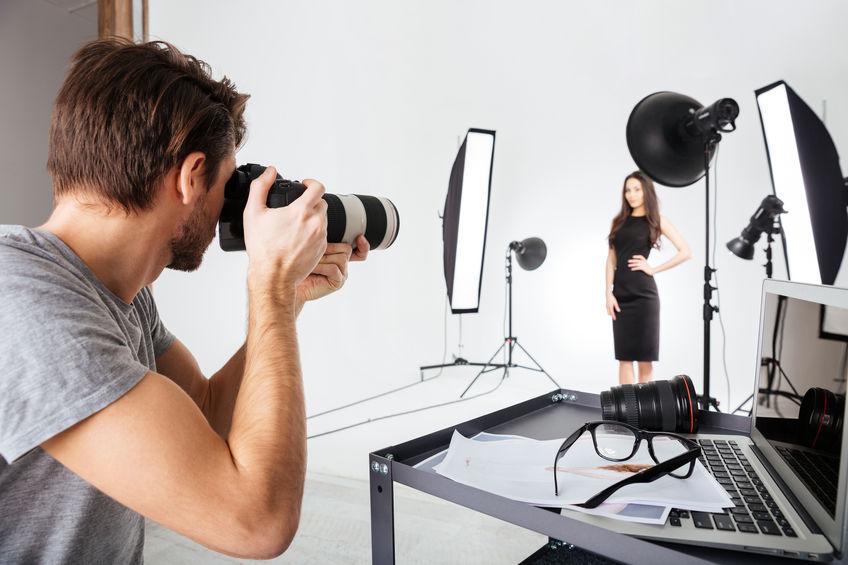 Na foto um fotógrafo tirando fotos de uma modelo.