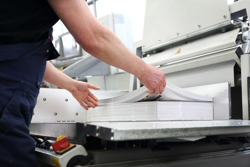 Imagem mostra uma pessoa cortando uma grande quantidade de papéis de uma só vez em uma guilhotina.