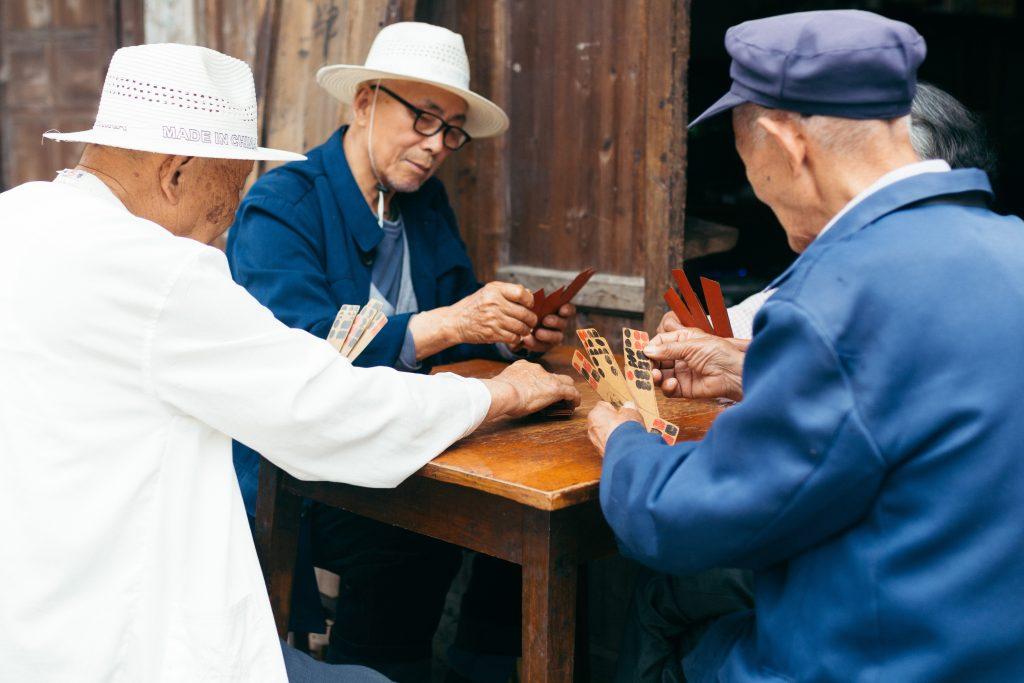 Imagem mostra três pessoas sentadas ao redor de uma mesa quadrada, jogando um jogo e manuseado fichas retangulares.