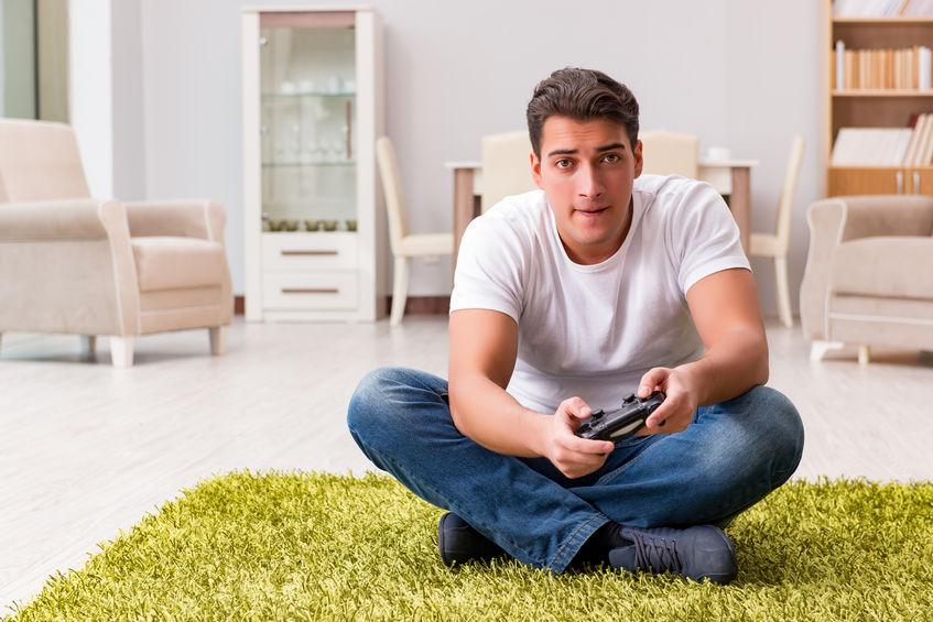 Imagem mostra um rapaz sentado no tapete de sua casa, manuseando um controle de videogame com entusiasmo.
