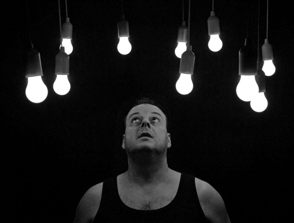 Homem olha para diversas luminárias de teto
