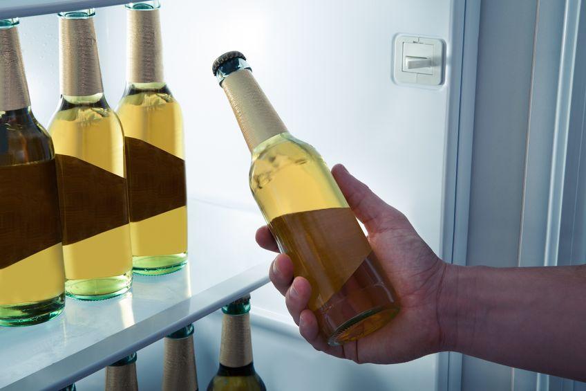 Mão de homem pegando garrafa na mini geladeira.