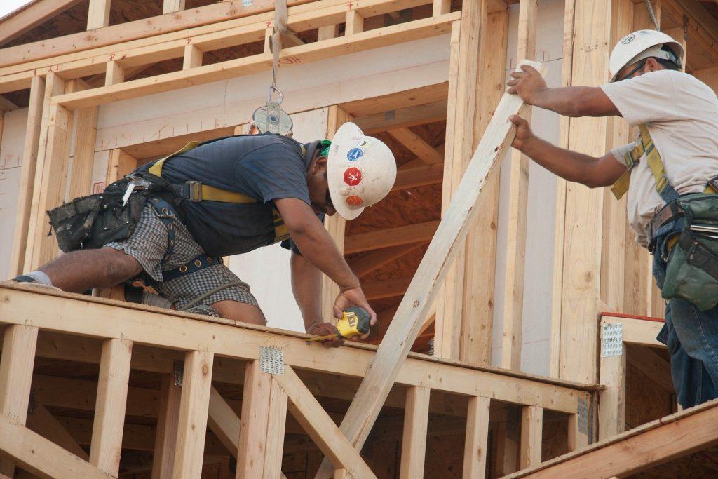 Imagem mostra dois homens trabalhando em construção civil e usando uma furadeira.